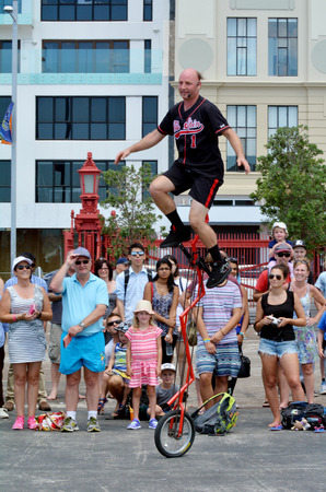 practiced: AUCKLAND,  NZL - JAN 30 2016:Man ride unicycle during a street performance.Unicycling is practiced professionally in circuses, by street performers, and in festivals.