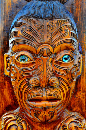 migrated: AUCKLAND,  NZL - JAN 30 2016:Maori man face wood carving sculpture. Maori are the indigenous people of New Zealand. Originally from Polynesia, Maori migrated to New Zealand over 1000 years ago.