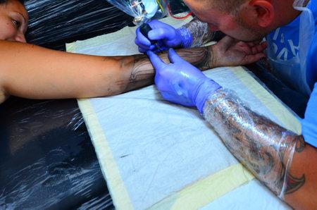 exceptionally: AUCKLAND,  NZL - JAN 30 2016:Maori Tattooist artist tattoo Ta moko on a Maori woman arm.The Tohunga ta moko tattooists were considered tapu, or exceptionally inviolable and sacred.