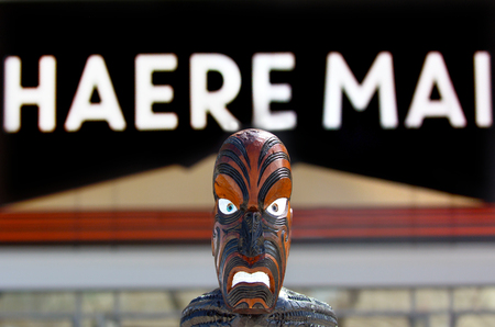 migrated: AUCKLAND - JAN 30 2016:Maori sculpture under a sign reads Welcome in Maori Haere Mai Maori are the indigenous people of New Zealand that migrated to New Zealand from Polynesia1000 years ago.