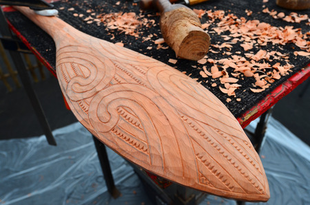maori: AUCKLAND,  NZL - JAN 30 2016:Maori Taiaha wood curving. It is a traditional weapon of the Maori of New Zealand, Originally from Polynesia, Maori migrated to New Zealand over 1000 years ago.