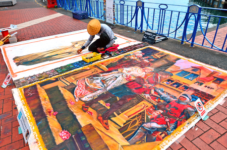 street painting: AUCKLAND,  NZL - JAN 30 2016:Street artist drawing on the floor Street painting.The origins of modern street painting can be traced to Britain. Pavement artists were found all over the United Kingdom and by 1890 it was estimated that more than 500 artists