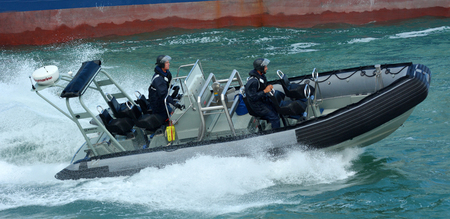 inflatable boat: AUCKLAND, NZL - JAN 30 2016:Royal New Zealand navy sailors ride a Zodiak Rigid-hulled inflatable boat in ports of Auckland.The RNZN has a role to help prevent any unrest occurring in New Zealand.