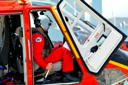 helicopter pilot: AUCKLAND - JAN 31 2016:Rescue Helicopter pilot sit in the cockpit. The median yearly income for a helicopter pilot is around 85,000. However, helicopter pilots on the top end will make over 105,000.