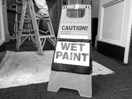 redecoration: Hazard sign reads: Caution Wet Paint. Renovation and construction concept