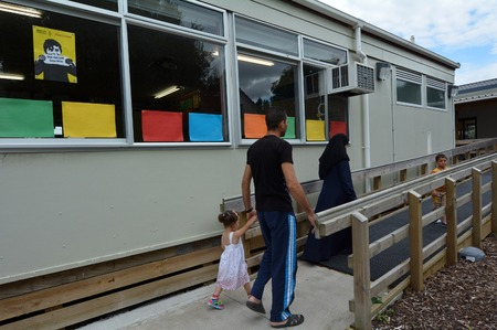 war refugee: Auckland, New Zealand - February 21, 2016: A Syrian refugee family walks into school at the Mangere Refugee Resettlement Centre.New Zealand annual intake is 750 refugee but accepted extra 600 people fleeing war in Syria. Editorial