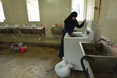 war refugee: Auckland, New Zealand - February 21, 2016: A Syrian refugee woman does her laundry in the laundry room at the Mangere Refugee Resettlement Centre.New Zealand annual intake is 750 refugee fleeing war in Syria. Editorial