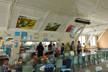 syrian war: Auckland, New Zealand - February 21, 2016: Syrian refugees eat lunch at Mangere Refugee Resettlement Centre.New Zealand annual intake is 750 refugee but accepted extra 600 people fleeing war in Syria.