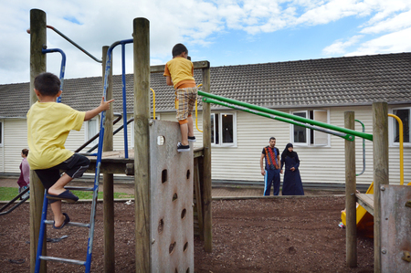 war refugee: Auckland, New Zealand - February 21, 2016: Syrian refugee couple watch their children play on a playground at the Mangere Refugee Resettlement Centre.New Zealand annual intake is 750 refugee fleeing war in Syria. Editorial