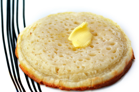 anglo saxon: A buttered English crumpet close up. Its a griddle cake made from flour and yeast. Stock Photo