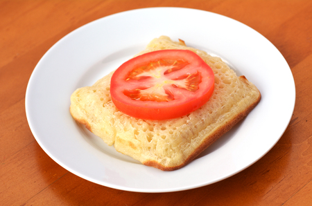 anglo saxon: Square shape buttered English crumpet with slice of tomato.Its a griddle cake made from flour and yeast. Stock Photo