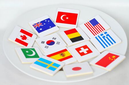new world order: International flags of the world served on a white plate. Foreign relationship police and a New World Order concept