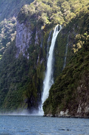 fiord: Spectacular waterfall in Milford Sound fiord, New Zealand. Stock Photo