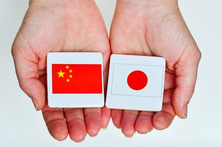 foreign national: Two hands holds the national flags of the Republic People of China (L) and Japan (R) beside each other on a white background. Foreign relationship policy concept