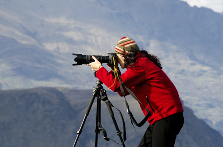 documenting: Professional on location and nature photographer woman photographing landscape  outdoor. Stock Photo