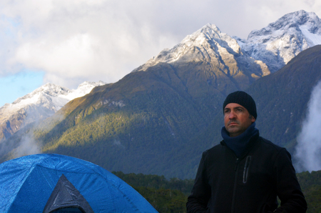 tough man: Portrait of a tough man camping outdoors under a high snow-capped mountain during sunset.