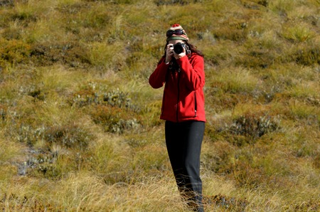 documenting: Professional nature and landscape photographer woman at work outdoor on location.