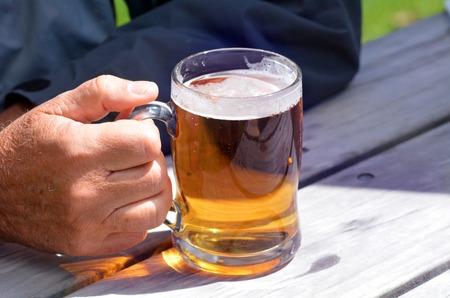 beer tap: Man hands holds Mug of beer.