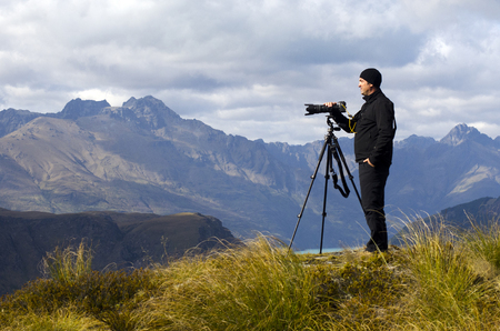 documenting: Professional nature and landscape photographer man at work outdoor on location. Stock Photo