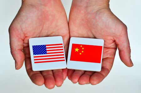 Two hands holds the national flags of the United States of America (L) and of the Republic People of China (R) beside each other on a white background. Foreign relationship policy concept