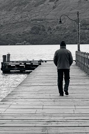 wharf: Mature man walks on a wooden wharf in a lake.
