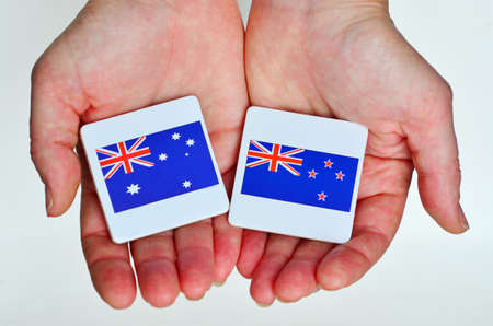 foreign national: Two hands holds the national flags of Australia (R) and New Zealand (L) beside each other on a white background. Foreign relationship policy concept