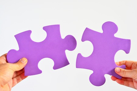Man and woman hands holds two different puzzle pieces separated on a white background.Relationship concept
