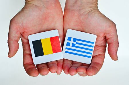 foreign national: Two hands holds the national flags of Germany (L) and Greece (R) beside each other on a white background. Foreign relationship policy concept