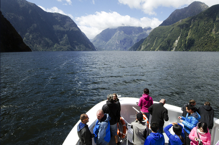 MILFORD SOUND,NZ - JAN 14:Visitors sail in Milford Sound on Jan 14 2014.It has been judged the worlds top travel destination in the 2008 Travelers Choice Destinations Awards by TripAdvisor.