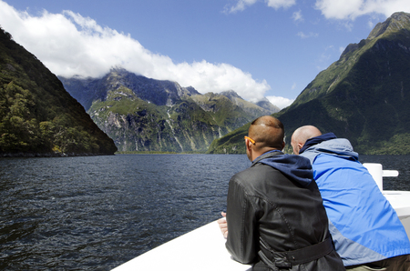 judged: MILFORD SOUND,NZ - JAN 14:Visitors sail in Milford Sound on Jan 14 2014.It has been judged the worlds top travel destination in the 2008 Travelers Choice Destinations Awards by TripAdvisor.
