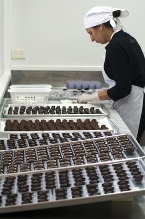 crave: KERIKERI, NZ - JAN 07: Chocolate factory worker prepares dipped Chocolate balls on Jan 07 2014.More than twice as many women than men eat and crave chocolate.