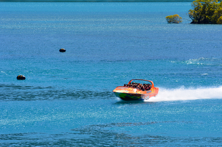 nz: QUEENSTOWN, NZ - JAN 15:Tourists enjoy a high speed jet boat ride on Jan 15 2014 in Queenstown, New Zealand. Queenstown is one of the most popular summer and winter resort in NZ.