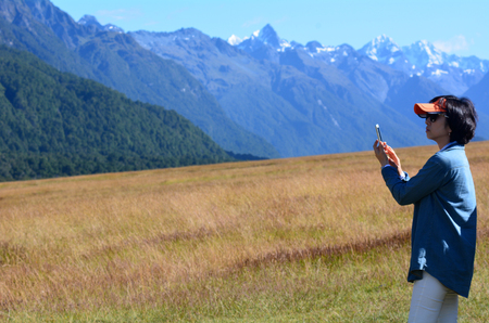 contributing: FIORDLAND, NZ- JAN 14:Asian tourist visit in Fiordland on Jan 14 2014.Tourism is an important industry in New Zealand, directly contributing NZ7.3 billion or 3.7 of the countrys GDP in 2013 Editorial