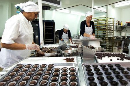KERIKERI, 뉴질랜드 - 1 월 07 : 초콜렛 공장 노동자는 1 월 07 일 2014 년에 담근 초콜렛 공을 준비합니다. 2006 년 6 백 5 십만 톤 이상의 초콜릿이 전 세계적으