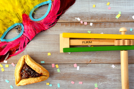 purim: Flat lay of Purim Jewish holiday food and objects: hamantaschen, wooden Purim gragger and carnival mask. Copy text space.