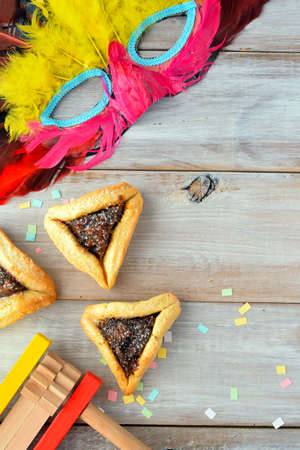 purim mask: Flat lay of Purim Jewish holiday food and objects: hamantaschen, wooden Purim gragger and carnival mask. Copy text space.