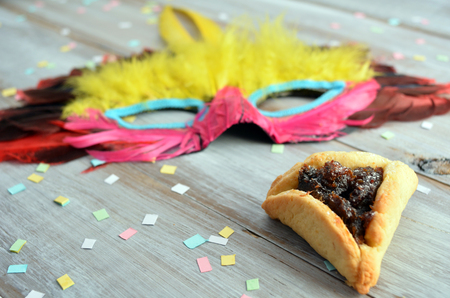 purim mask: Purim Jewish holiday food and objects: hamantaschen, wooden Purim gragger and carnival mask on a wooden table.Copy text space.