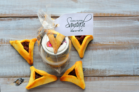 manos: Flat lay of Purim basket (Mishloach manot) in side a Star of David made out of Purim Cookies - Hamentashen (Ozen Haman) for Purim Jewish Holiday. Copy space
