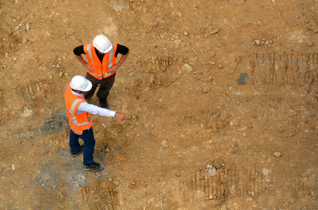 Aerial view of two unrecognised civil engineers inspecting construction site. Building development concept with copy space Editorial