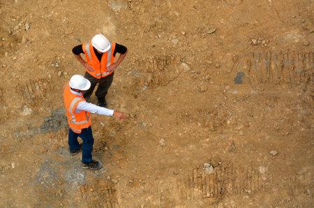 cenital: Vista aérea de dos ingenieros civiles no reconocidas inspección de emplazamiento de la obra. Construir el concepto de desarrollo con el espacio de la copia Editorial
