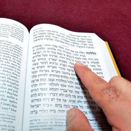 siddur: Jewish man finger reads from Jewish prayer book. Judaism concept with copy space Stock Photo