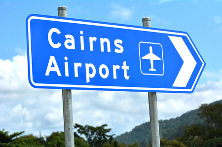 cairns: Cairns airport traffic sign in Queensland Australia against the Atherton Tableland mountains region.