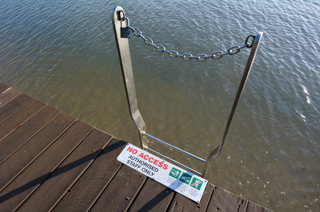 stingers: Ladder to water with locker and chain and a No access to water signs and symbols in the tropical north of Queensland, Cairns esplanade , Australia. Stock Photo
