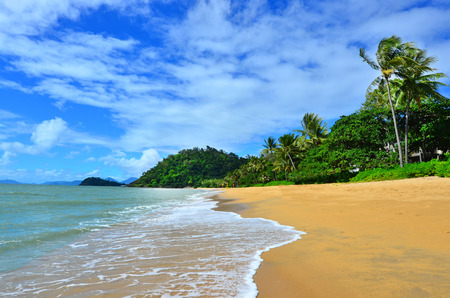 A couple walks on Trinity beach near Cairns in Tropical North Queensland, Queensland, Australia.