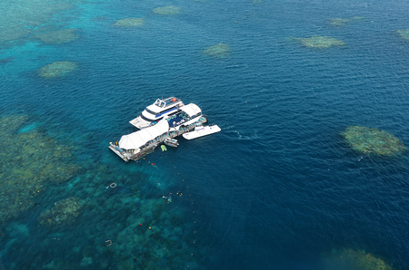 barrier: Aerial view of reef with all-weather marine diving platform and boats at the Great Barrier Reef worlds largest coral reef system, near Cairns Queensland Australia.