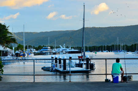 Fisherman fishing from the Sugar Wharf in Port Douglas in the far north of Queensland,  Australia. Stock Photo