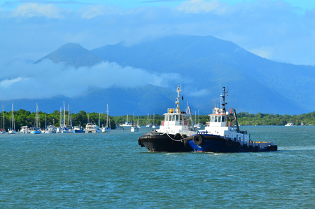 CAIRNS, AUS - APR 15 2016:Two tugboats sail  at the entrance to Trinity Inlet, a significant location of Cairns city sea port.