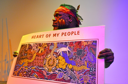 australian ethnicity: QUEENSLAND - APR 16 2016:Indigenous Australian man explain about the significant of the art Dot painting. Its one of the oldest traditional form of art in the world of marks to tell Aboriginal myths