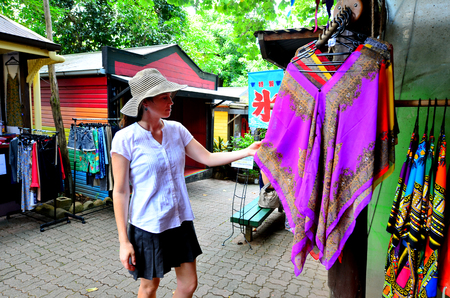 tableland: CAIRNS, AUS - APR 17 2016:Woman shopping clothes at the Original Rainforest Market a popular travel destination in Kuranda at the Atherton Tableland tropical north of Queensland, Australia Editorial