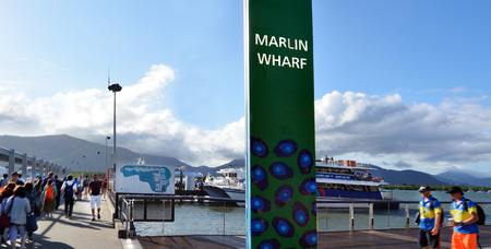 cairns: CAIRNS, AUS - APR 15 2016:Visitors boarding on a cruise boat in Cairns Marlin Marina in Queensland Australia, a significant departure location of tourism tours to the Great Barrier Reef. Editorial